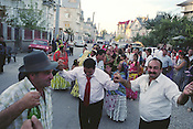 The Tomita family, with friends and relatives, dance on the road outside their house, on the day of the baptism of grandson Sarion Bratu Badea. The party was to last for 12 hours. They dance on the road that runs through the centre of the Roma camp of SIntesti.