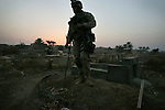 Combat Engineers and Marines with 3rd Platoon Golf Company 2nd Battalion 5th Marines search a cemetery and nearby park for hidden weapons caches on January 17, 2005 in Ramadi, Iraq. The search resulted in the discovery of several mortar rounds which were destroyed in place.