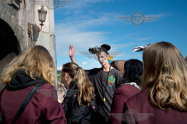 A group of schoolgirls are 'greeted' by a member of staff at 'Cinderella's Castle', created by artists Block9, on show at Dismaland, artist Banksy's play on the ammusement park experience. Work by 50 artists was on display over the summer at Bemusement Park, a derelict lido on the seafront.