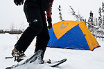 A man walks in snowshoes near a Sierra Designs tent.