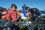 A refugee girl stands amid discarded life jackets after landing in an overcrowded rubber raft on a beach near Molyvos, on the Greek island of Lesbos, on November 2, 2015. She and her family and the other refugees crossed the Aegean Sea from Turkey and were received by local and international volunteers. They then proceeded on their way toward western Europe. The boat was provided by Turkish traffickers to whom the refugees paid huge sums to arrive in Greece.