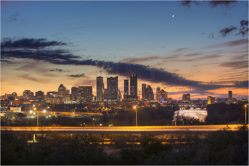On a crisp February Morning, the moon was high in the sky and the first orange light of sunrise was creeping up in the sky over Austin, Texas. In this image of Austin, you can see Austin Landmarks such as Congress Bridge, Lamar Bridge, and the First Street Bridge, along with the Austonian, 360 Condos, the Springs Condominiums, with MoPac spanning Lady Bird Lake in the foreground.