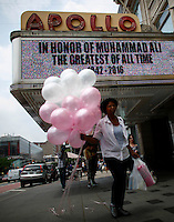 NEW YORK CITY, NY - JUNE 4: A woman walks while she carries ballons in Harlem as Muhammad Ali's death news is display on screens at the Apollo theater on June 4, 2016 in Manhattan, New York. Ali died at a Phoenix-area hospital, where he had spent the past few days being treated for respiratory complications. Photo by VIEWpress