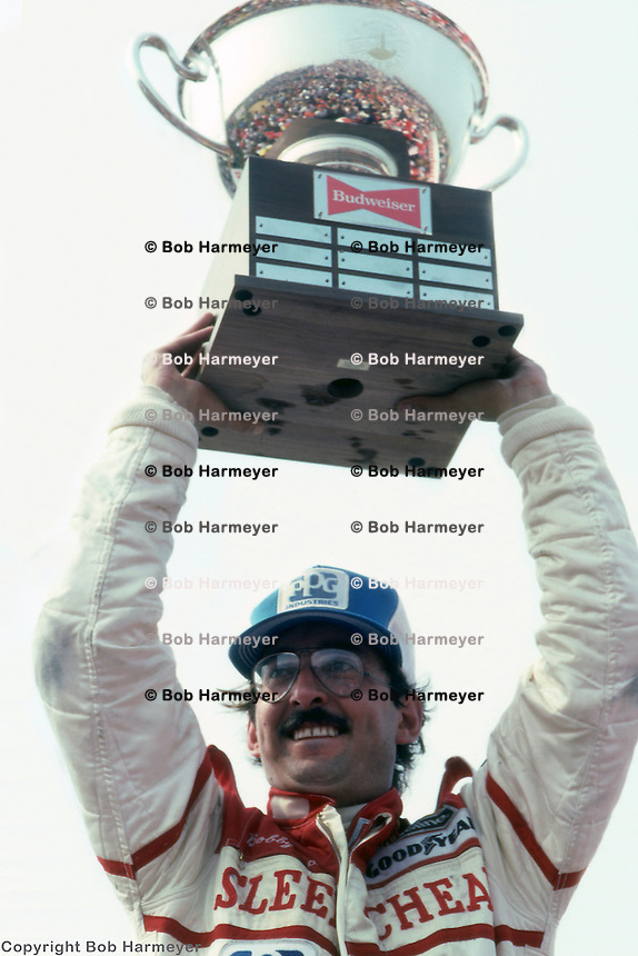 CLEVELAND, OH - JULY 4: Bobby Rahal celebrates with the trophy in victory lane after winning the CART Indy Car race on July 4, 1982, at Burke Lakefront Airport in Cleveland, Ohio. It was Rahal's first Indy Car victory.