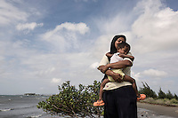 """Indonesia – Sumatra – Banda Aceh - Lam Manyang – Lisma, 29-year-old holding her three-year-old daughter.  """"I still have recurrent nightmares about the tsunami. I see the waves coming back again"""". Lisma was able to meet the rest of her family only three days later, in the house of a relative. Her mother and two of her sisters were missing and were never found. """"For the first two years we kept on expecting them back. Then we gave up"""" she says. """"The tsunami helped me become a better person"""" she concludes. """"Before I was young and dismissive of any advice my parents would give me. Only when I lost my mother I realized the importance of what she taught me""""."""