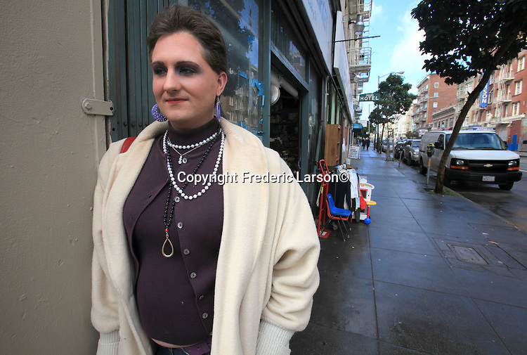 """Serenity""  who just arrived in San Francisco from Oklahoma City poses for a photograph along a storefront window in the Tenderloin district of San Francisco, California."