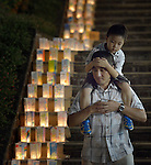 A father and son inspect candles lining a path in Nagasaki, Japan, on August 8, 2015, the eve of the 70th anniversary of the U.S. bombing of the port city with an atomic bomb. The candles represent a memorial to those who died and a prayer for peace, including an end to nuclear weapons.
