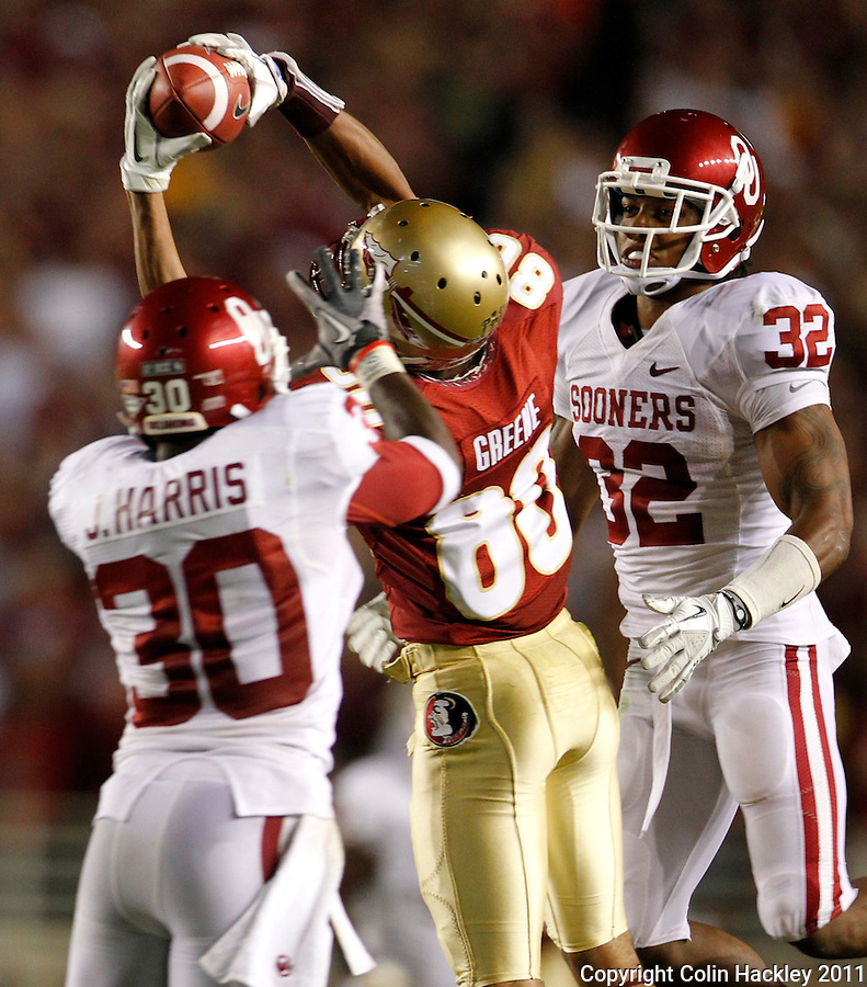TALLAHASSEE, FL 9/17/11-FSU-OU091711 CH-Florida State's Rashad Greene makes a touchdown between Oklahoma's Javon Harris, left, and Jamell Fleming during second half action Saturday at Doak Campbell Stadium in Tallahassee. The Seminoles lost to the Sooners 23-13..COLIN HACKLEY PHOTO
