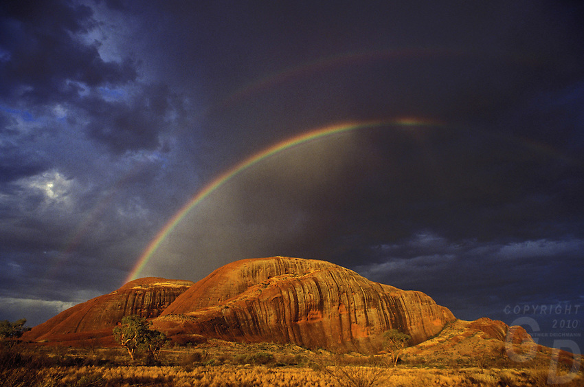 A rare Rainbow over the Olgas, Northern Territory in Central Australia.<br /> It is believed that this is the first and only image ever taken with a rainbow over the Olgas until now. An award winning image published many times shot on Kodachrome film.<br /> it was also use on the Cover of &quot;Die letzten Nomaden&quot; in 2007 by<br /> ARAKI PUBLISHERS, Germany published the book Die letzten Nomaden - The last Nomads of Australia by international Author William J.Peasley the book has been published numerous times in Australia and the Documentary Film received in 1997 a Gold medal at the New York Film Festival. Cover Photo by Gunther Deichmann, a well known and multi awarded image of the Olgas with a Rainbow taken in the Northern Territory of the Australian outback.