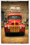 Classic old red truck parked in front of a Mobilgas sign.