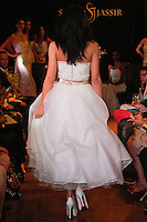 Model walks the runway in a Pearl wedding dress - crochet lace and silk organza tea length gown, by Sarah Jassir, for the Sarah Jassir Couture Bridal Fall 2012 Opulence collection.