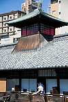 A bather hangs out his towel on the balcony outside the 2nd floor rest area at  Dogo Onsen, thought to be Japan's oldest spa in Matsuyama City, Ehime Prefecture, Japan on 20 Feb. 2013.  Photographer: Robert Gilhooly