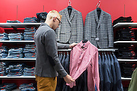 Teenager boy choosing shirt in retail shop Tartu Kaubamaja in Estonia. Jeans on shelves.