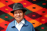 South America, Ecuador, Otavalo. A weaver of Peguche stands in front of his work at the Otavalo Market.