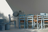Wooden chairs and wicker baskets on the terrace have been given the same blue and white paint effect