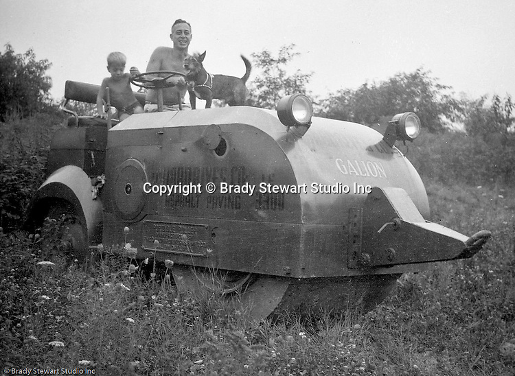 Mt. Washington:  View of Father, son and dog sitting on road paving equipment used during the construction of Chatham Village in Pittsburgh - 1934.  This was a gas-driven roller but if it ran out of gas, it could be pulled by another vehicle (see front hook).