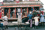 Traders selling goods and products to people waiting on a colourful  bus. Images of the capital,Port au Prince,  Haiti 1975
