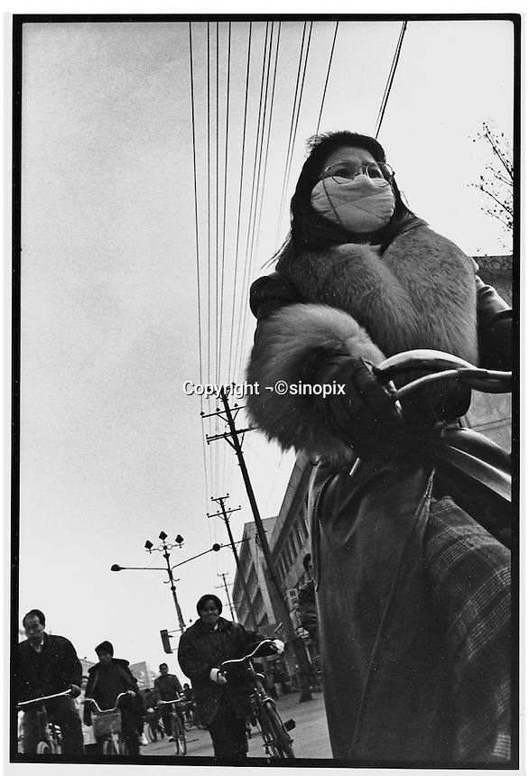 Masked and wrapped-up against the cold. A lady cycles to work in Beijing...PHOTO BY WANG TONG / SINOPIX