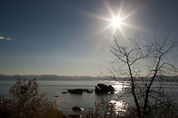 """Solar Eclipse Above Tahoe"" - Photograph of the solar eclipse above Whale Rock at Lake Tahoe. You can't see the eclipse in the sun but you can see it happening in the lens flare on the bottom left of the sun."