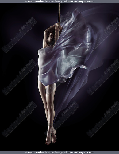 Sensual dynamic dream-like photo of a beautiful young naked woman with tied ankles and flowing cloth wrapping her nude body, suspended on a bondage rope by her hands on black background
