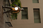 Sculpture of man walking on side of wall carrying a lamp at the Pike Place Market