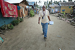 Leopold Sindayigaya, a water and sanitation advisor for Norwegian Church Aid, walks along the main street in Bacubac, a seaside neighborhood in Basey in the Philippines province of Samar that was hit hard by Typhoon Haiyan in November 2013. The storm was known locally as Yolanda. Norwegian Church Aid, a member of the ACT Alliance, is sponsoring the construction of bathrooms with septic systems for houses in the village where existing systems were destroyed by the typhoon's unusually high storm surge.