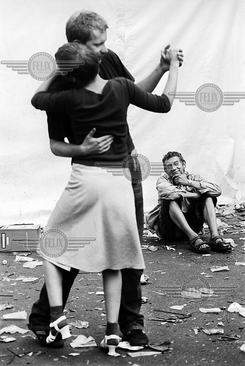 Two young people dancing during the Ghent Festival while another man looks on.