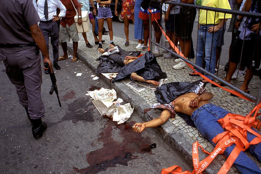 Crowds form around the bodies of two thieves killed by Rio de Janeiro state police after the men robbed a nearby pharmacy. One police officer was charged with murder in the illegal street-side executions which were captured by TV cameras at the scene.