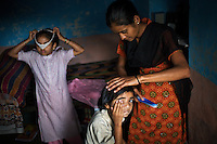 Vasanti Shinde, age 26, who is HIV positive, at home with her daughters Vrinda, 8 and Shruda, 10. Shinde works for the Save Foundation which represents the rights of HIV positive people. ...Like many of the women who work for and with the Save Foundation, Vasanti Shinde, age 26, only found out that she was HIV positive after her husband became seriously ill with an AIDS-related illness five years ago. Vasanti's husband subsequently died. Vasanti now lives with her two younger daughters Shrudha, age 10, and Vrinda, 8, in the one-room home of her brother in Sangli city. Vasanti's elder daughter, eleven year old Shubhada is being brought up by her paternal grandmother and sees her mother during holidays. Vasanti knows that Shubhada is HIV negative and Shruda is positive but anxiety over the result means that she refuses to have Vrinda tested for HIV. For a monthly income of Rs.3500, Vasanti works as a field officer and counselor for the Save Foundation. She works in the positive-people's pharmacy for no pay. Her work with the Save Foundation entitles her access to a credit union which provides low interest loans covering medical expenses. Though first-line drugs and homeopathic medicine keep Vasanti healthy, she is prone to infection and recently suffered a bout of influenza. Vasanti is completely open about her HIV status and most of her neighbours know that she is HIV positive. Vasanti says that &quot;I used to feel like I was going to die. Now, because of the Save Foundation, I feel like I'm going to live.&quot; ..Photo: Tom Pietrasik.Sangli, Maharashtra. India.August 28th 2008.