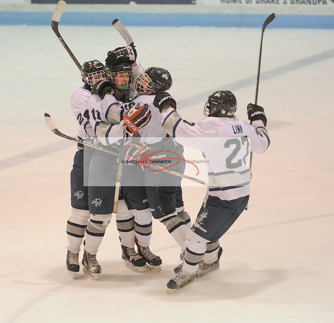 Eagle River's Sutton McDonald, center, is mobbed by teammates Connor Canterbury (24), Ty McEnaney (9) and Joshua Linn following his third-period goal at Ben Boeke Arena Tuesday, February 2, 2016.  Photo for the Star by Michael Dinneen