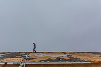 Roofer walks along the peak of a roof weedy for new shingles.