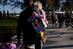 Andrew Jones carries his daughter Hannah Jones, 5, with his other daughter Ava Jones, 3, left, after a long day at Legoland in Whitehaven, Florida on February 11, 2012.