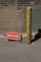 A sign lays at the side of an alleyway ready for deployment
