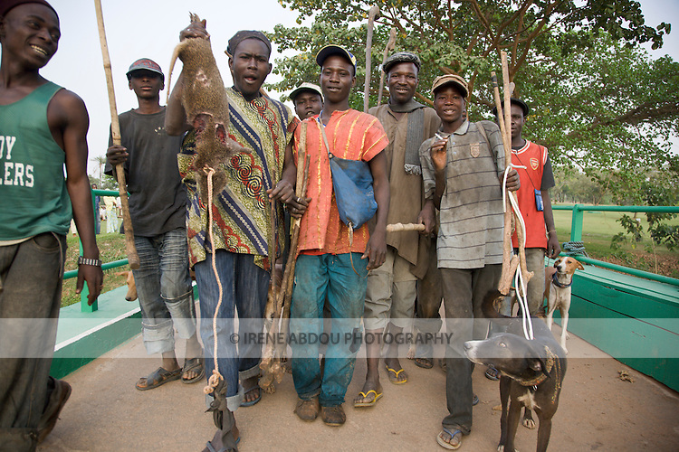 A group of hunters, one carrying a bush rat kill, pass through Abuja's Millenium park on their way home at the end of the day.