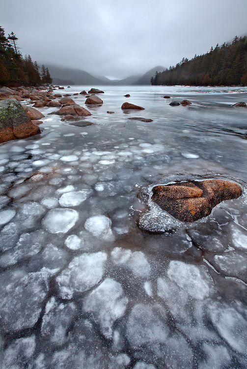 Frozen ice atop Jordan Bond with the Bubbles peaking out of the winter fog on Mount Desert Island in Acadia National Park, Maine, USA