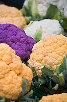 Purple, white and orange Cheddar cauliflowers at a farmers market.