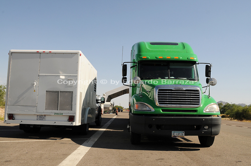 "Nogales, Arizona - A Border Patrol vehicle (left) utilizing mobile X-ray technology and operated by a CBP inspector analyzes the contents of this semi-truck at a permanent traffic checkpoint located on highway Interstate 19, north from Nogales and near the Town of Tubac, Arizona. ""See-through"" mobile X-Ray units allow officers to get a picture of the contents of a vehicle being searched. Border Patrol checkpoints serve as inspection stations to detect illegal immigration and drug smuggling. Border Patrol agents assigned to fixed traffic checkpoints have wide discretion to stop vehicles for brief questioning and inspection of its occupants and its contents. This checkpoint is part of the Border Patrol Tucson Sector. Photo by Eduardo © 2012"