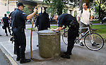 July 18, 2003 -The Grim Reaper has his scythe confiscated by Portland Police as a safety concern. He was one of many protestors take to the streets about the Federal Courthouse to show their displeasure of the visit of U.S. Attorney John Ashcroft.