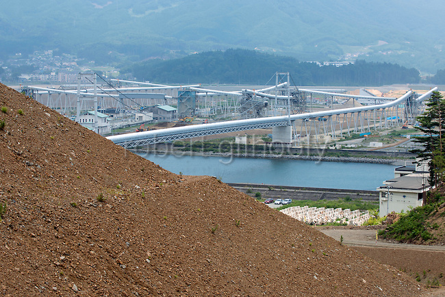Photo shows the rebuilding project in Rikuzentakata, Iwate Prefecture, Japan. Atlas Copco drill rigs are a key feature of the project, which will shift blasted rubble from a nearby hillside to the central part of the city via a 3-km-long conveyor belt. Rikuzentakata was flattened by the March 2011 tsunami and the rebuilding project aims to raise the land near the coast by 10 meters. Rob Gilhooly Photo