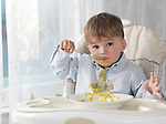 Cute baby boy sitting in a high chair and eating soup with a spoon, spilling it on his shirt