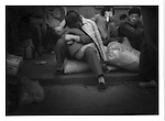 Migrant woman cradles her child in the Beijing Train Terminal.  Beijing, China.   1994