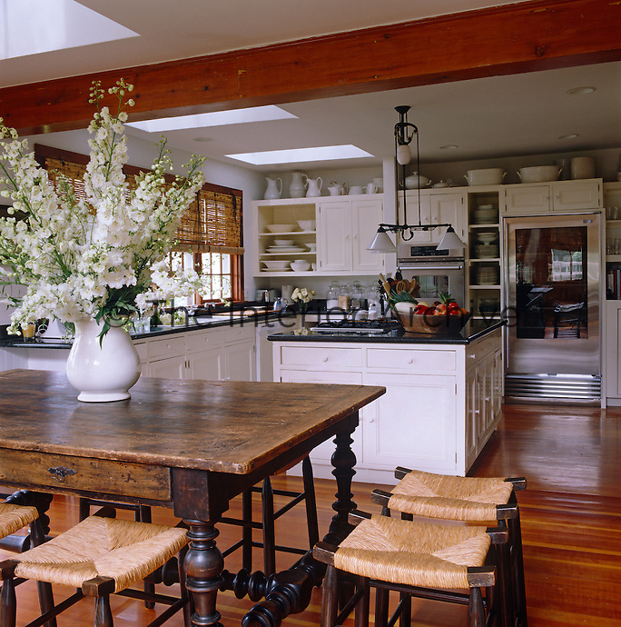 The kitchen has the feel of a farmhouse kitchen with a large wooden table and stools with cane seats
