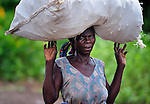 "A woman carries a bag on her head as she walks in Chidyamanga, a village in southern Malawi that has been hard hit by drought in recent years, leading to chronic food insecurity, especially during the ""hunger season,"" when farmers are waiting for the harvest."