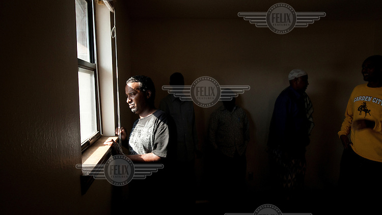 A Somali man looks out of the window of the town's mosque in Garden City, Kansas. He is one of the many migrants who have come to the town to work at the Tyson meat packing plant. This facility kills and processes between five and six thousand beef cattle every day. Kansas dominates the American beef industry, producing 25% of all beef raised in the USA. However, the industry is heavily dependent on cheap immigrant labour.