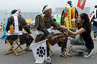 Participants being interviewed during the Somanomaoi Festival, Minami-soma City, Fukushima Prefecture, Japan, July 27, 2013. During the four-day-long Somanomaoi Festival members of old samurai families ride horseback through the town in traditional armour.  They also take conduct ceremonies at local shrines, take part in horse races, and compete on horseback to catch a flag launched into the air by fireworks.