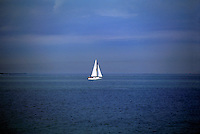 Seascape of a sailboat sailing in light winds on an overcast, grey day. Sky and sea are nearly the same color with the white sail as contrast.