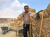 15. &quot;Workman repairs walls of Masada&quot;: Judean Desert.<br /> <br /> The notion of repairing, like returning, is central to Jewish thought. These concepts are reiterated each Rosh Hashanah (New Year), for example. So for me, the eloquent gesture of golden sand streaming through this workman's hands as he repairs Masada, a place Jews return to because it resonates with resistance and freedom, seems especially apt.<br /> <br /> Masada is a UNESCO World Heritage Site. Located on an austere desert bluff high above the Dead Sea, it was the dramatic setting for a pitched battle between Romans and Jews that in 73 CE ended with the Jews choosing suicide over slavery. As a result, Masada has become one of the Jewish People's greatest symbols -- if not of freedom, then certainly of zealous resistance to coercion.<br /> <br /> When I visited Masada, I climbed to the top on the more than two-thousand year old rocky path like my ancestors. While walking around the fort's remains, I filled my lungs with thin air, saw bright light and a vast space that felt almost cosmic. I met this workman applying earth, like a plaster, to the crumbling walls. The earth was ochre and looked precious, like gold. Spontaneously, the man reached down and scooped up the sand with his hands: &quot;This is Eretz Y'Israel, the land of Israel,&quot; he seemed to say. As the sand streamed through his fingers, he smiled at me.