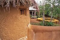 "Carol Anthony's adobe ""santuario"" is embelished by a roof of twigs and a thick stucco wall which embraces it and her small  tin roofed casita."