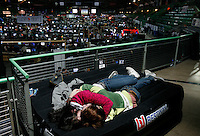 A couple resting in a corner. One of the world's largest convention of computer enthusiasts, simply called 'The Gathering'. Over five thousand young people come together each Easter, some travelling long distances, each carrying their own computer equipment to the massive Vikingship sports hall in the city of Hamar. The main activity is online gaming. Many hardly see daylight or taste fresh air for the entire five days as they compete with their fellow geeks for cash prizes and the honour of being the best.