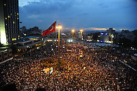 Protestors are seen under a Turkish flag in Taksim Square, Tuesday, June 4, 2013, in Istanbul, Turkey. (Seamus Travers/pressphotointl.com)